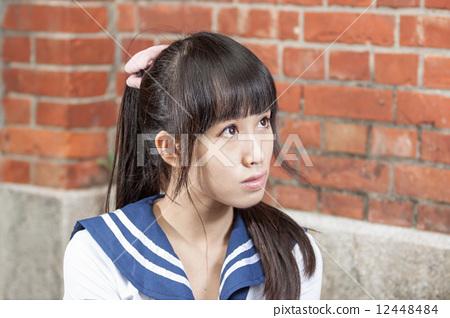 Asian schoolgirl in uniform outside school 12448484