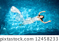 woman in long white dress swimming in pool at sunny day 12458233