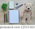 Blank paper, color paint and bear doll on the wood table - Top view 12531363