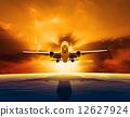 passenger jet plane flying over beautiful sea level with sun set 12627924