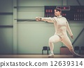Young woman fencer with epee 12639314