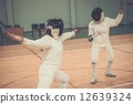 Two women fencers on a training 12639324