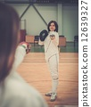 Young woman fencer and her trainer 12639327