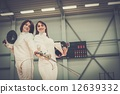 Young woman fencer and her trainer 12639332