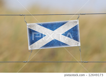 Border fence - Old plastic sign with a flag 12649173