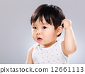 Surprised baby scratching head 12661113