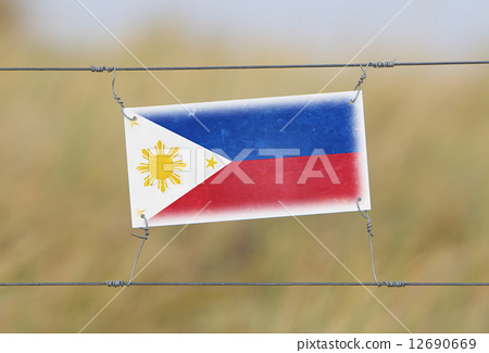 Border fence - Old plastic sign with a flag 12690669
