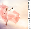 A woman wearing a pink dress with a lamp 12707253