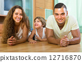Happy couple with child at home 12716870