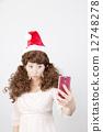 Girls wearing Santa cap wigs Take photos with smartphone 12748278