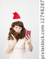 Girls wearing Santa cap wigs Take photos with smartphone 12748287