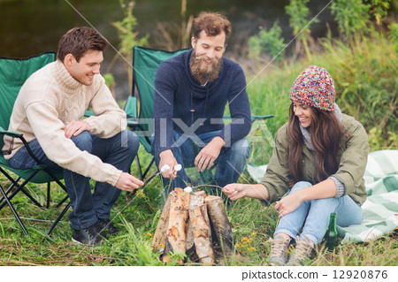 smiling tourists cooking marshmallow in camping 12920876
