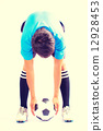 Soccer player holding a soccer ball preparing for penalty shot. 12928453