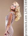 Graceful Woman in Retro Polka Dot Dress Looking Back 12973389