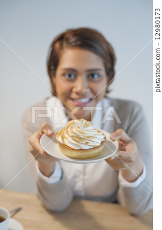 Asian lady enjoying her coffee and dessert at a cafe. 12980173