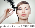 woman with mascara brush and black splash 12996180