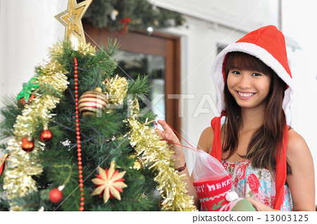 A beautiful Asian lady dressed with Santa Hat dressing up ...