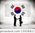 Two Businessmen Shaking Hands With Korean Flag As A Background 13036811