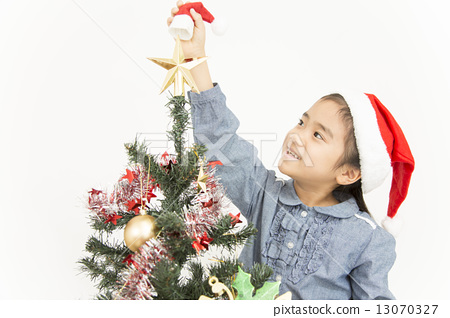 A girl decorating a Christmas tree 13070327