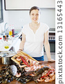 Happy woman cooking with seafood 13165443