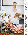 Happy woman cooking sea food specialties 13165497