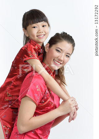 Young Chinese mother in cheongsam piggyback daughter isolated white background 13172292