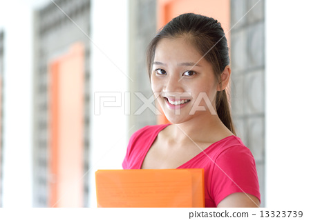 One young pan asian female student holding her notes file along campus corridor 13323739