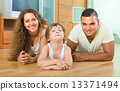 Happy couple with child at home 13371494