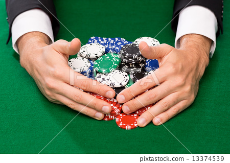 poker player with chips at casino table 13374539