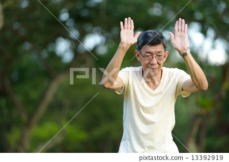 One male chinese elderly doing morning exercise in a park 13392919