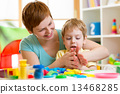 kid boy and mother playing colorful clay toy 13468285