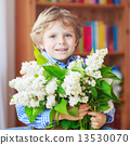 Adorable little toddler boy with blooming white lilac flower 13530070
