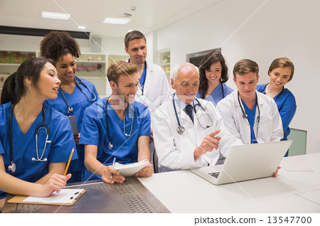 Stock Photo: Medical students and professor using laptop