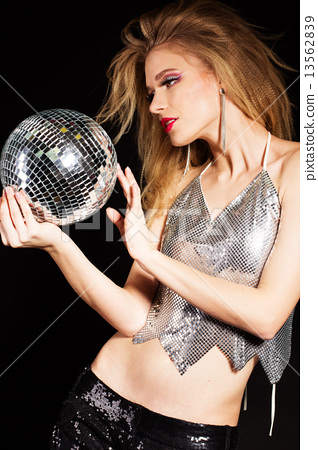 Fashion girl with disco ball over black background 13562839