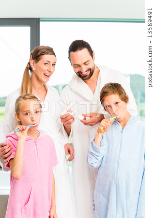 Family at dental care routine in bathroom 13589491