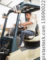 Driver operating forklift machine in warehouse 13690022