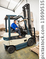 Driver operating forklift machine in warehouse 13690535