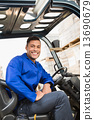 Driver operating forklift machine in warehouse 13690679