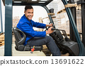 Driver operating forklift machine in warehouse 13691622