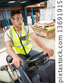 Driver operating forklift machine in warehouse 13691915