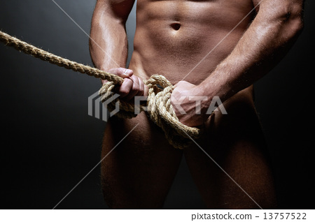 Studio shot of naked strong man tied with rope 13757522
