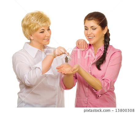 Senior woman giving keys to her daughter 13800308
