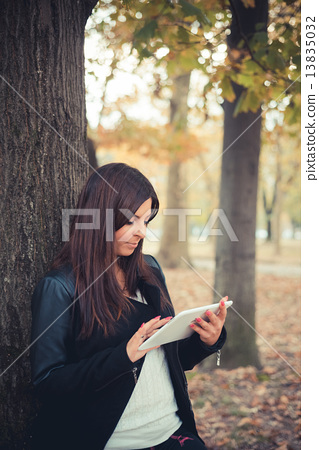 young beautiful brunette straight hair woman in the park 13835032
