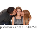 Parents kissing there daughter. 13848759