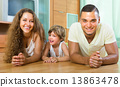 Happy couple with child at home 13863478