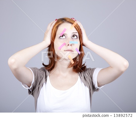 Confused red-haired businesswomen with notes on face. 13892572