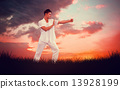 Composite image of handsome man in white doing tai chi 13928199