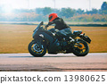 young man riding motorcycle in asphalt road curve with with a mo 13980625
