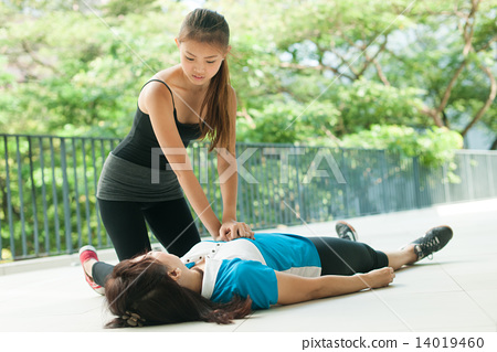 asian teenage girl doing cpr on middle aged woman 14019460