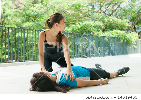 asian teenage girl doing cpr on middle aged woman and calling for help 14019465